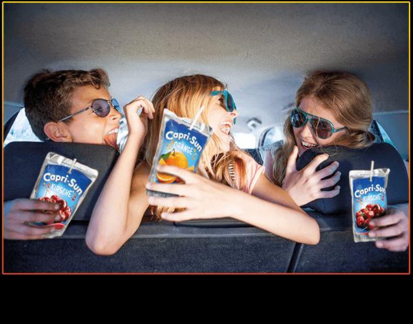 Kids in a car enjoying Capri-Sun Kirsche