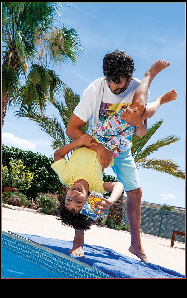 Kid upside-down holding Safari Fruit pouch