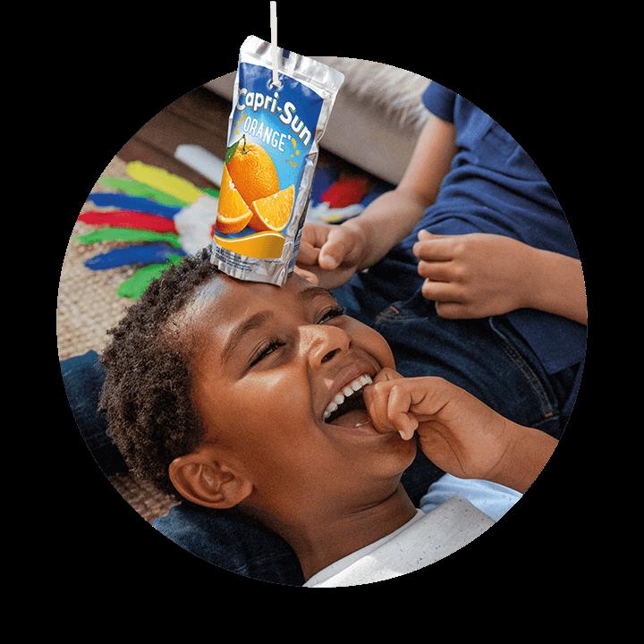 Kind mit Capri-Sun Beutel auf dem Kopf